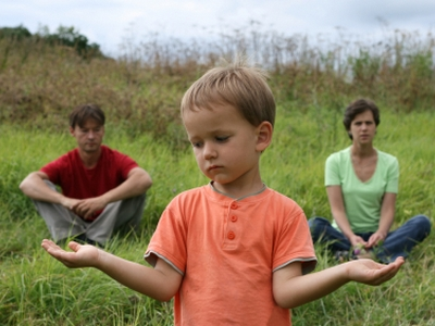 Boy holding his hands like scale choosing between his parents