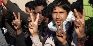Foreigners, said to be members of a human trafficking network smuggling illegal immigrants from Bangladesh and Somalia into Libya, flash the V-sign for victory as they gather in the courtyard of a prison where they have been held on the outskirts of the eastern Libyan city of Benghazi on March 15, 2012. Libyan security forces said they had dismantled the network, adding that the Bangladeshi ring leader confessed to bringing more than 200 illegal immigrants from his country in the past three months as the gang lured its victims with promises of safe passage and employment opportunities in the North African nation only to kidnap them in the hope of obtaining ransom payments from their relatives, according to Hussein al-Sahli, who headed the investigation.   AFP PHOTO/ABDULLAH DOMA