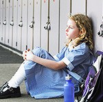 Elementary schoolgirl sitting on floor against school lockers Royalty free: For comercial usage price on demand