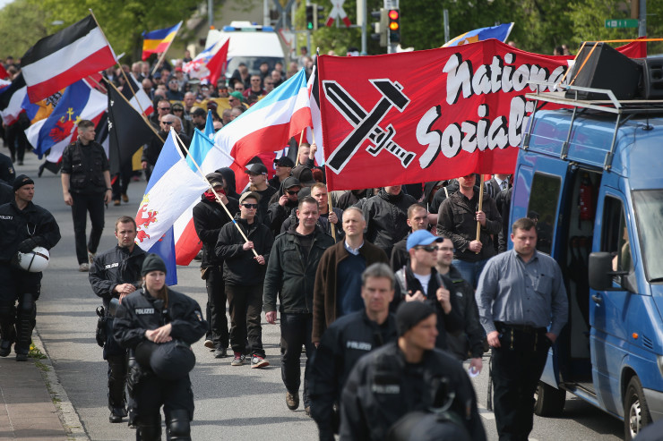 ROSTOCK, GERMANY - MAY 01:  Supporters of the far-right NPD political party, accompanied by riot police, march on May Day on May 1, 2014 in Rostock, Germany. Left-wing protesters repeatedly blocked the route of the approximately 250 NPD supporters and at one point attacked them with rocks. May Day gatherings and protests are taking place across Germany today and the one in Rostock was the NPD's main march.  (Photo by Sean Gallup/Getty Images)