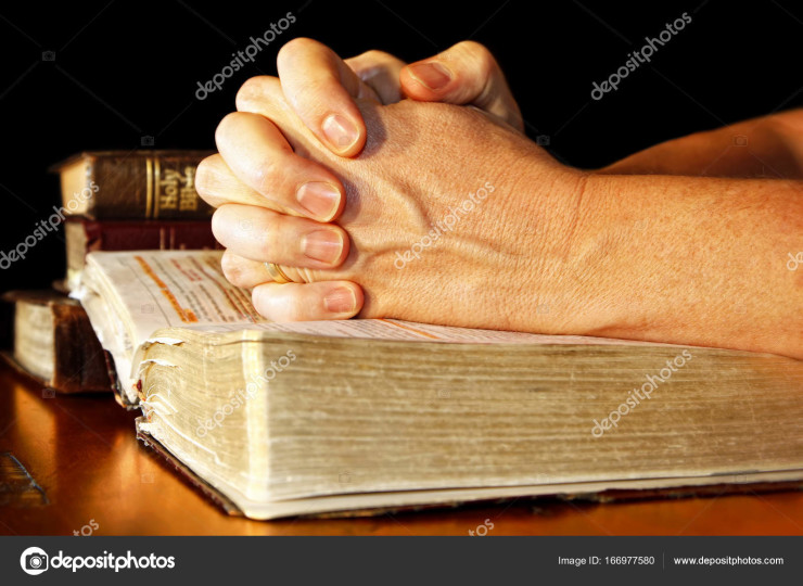 A man folds his hands in committed prayer over a Holy Bible, while light shines directly on his hands and the open bible.